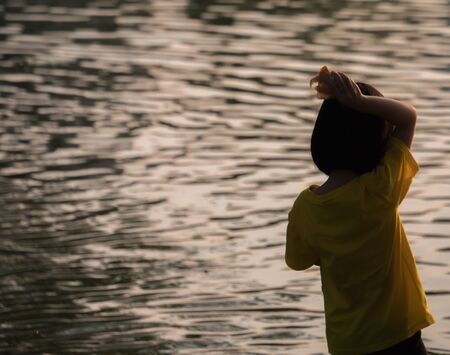 silhouette little girl in front of water with sunrise