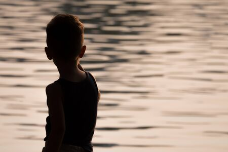 silhouette boy in front of water with sunrise