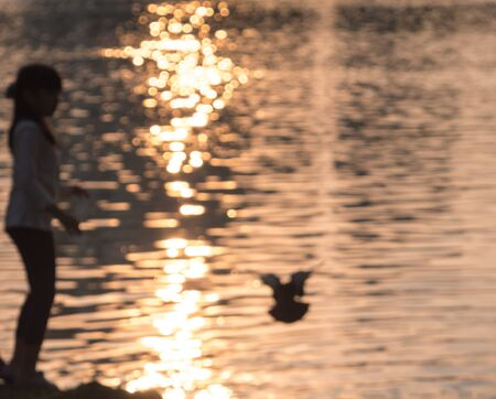 defocus of silhouette little girl in front of water with sunrise Foto de archivo - 131340966