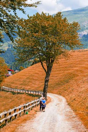 elderly couple walks on a mountain trail in autumn time, walking on Alps Stock Photo