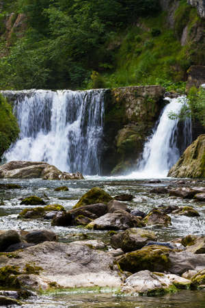 Mountain river with waterfall in summer time, alpine landscape