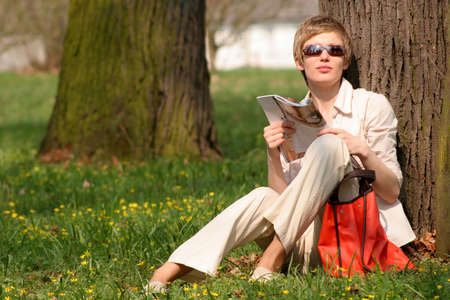 Young woman with magazine,sitting at the tree is havig sunbathe