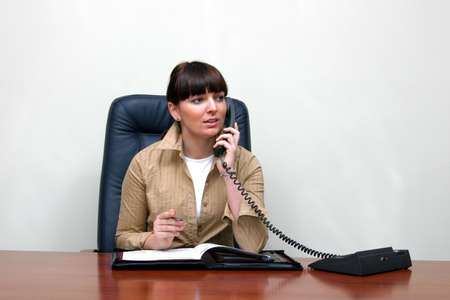 Adult white happy female in a white and roomy office talking on the phone and sitting behind a big brown desk . photo