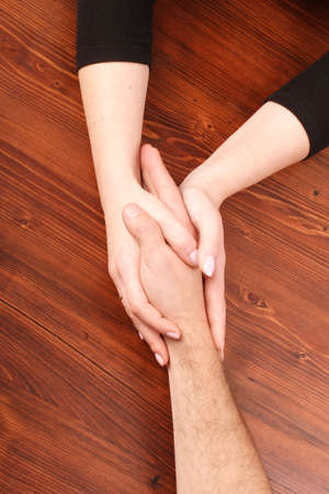 Womans hands holding mans hand Stock Photo