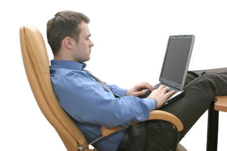Consultant sitting in leather armchair in relaxed position and working on his laptop