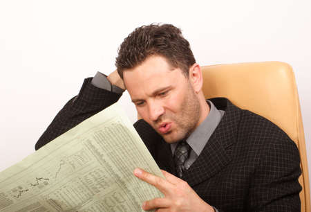 Worried handsome business man reading newspaper - portrait