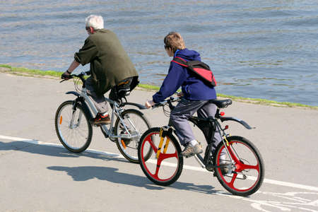 Father and son are riding on mountain bikes photo