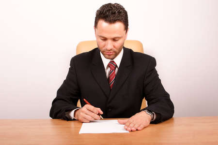 Handsome boss sitting at the desk with blank paper and pen in hand, signing a paper