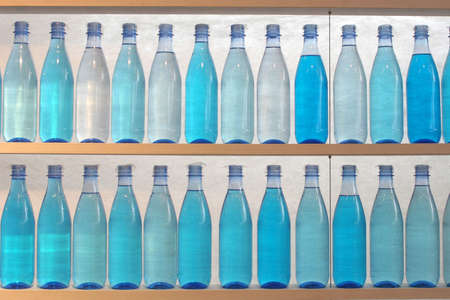 sip: Bottles filled with water, standing on the shelf - general