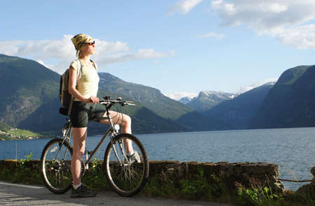 Healthy woman on her bike trip in the mountains over the lake