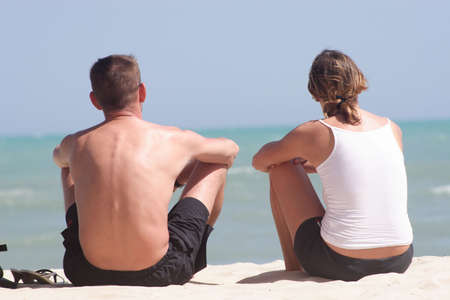 Adult white couple sitting on the beach