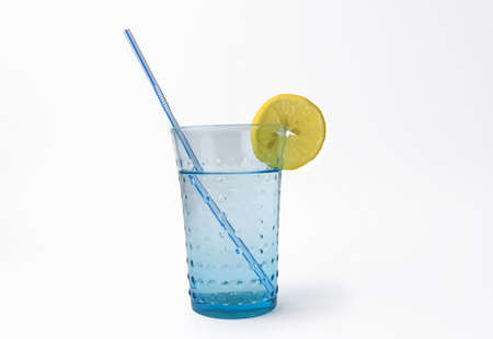 mineralized: glass of mineral water with lemon and straw on white background Stock Photo