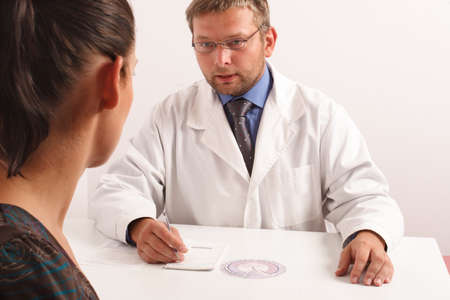 ailment: at the doctors office - doctor explainig diagnosis to his female patient Stock Photo
