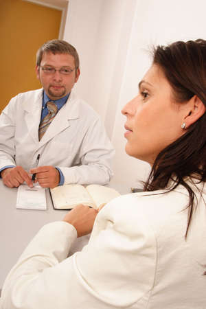 At the doctors office - doctor explaining diagnosis to his female patient photo