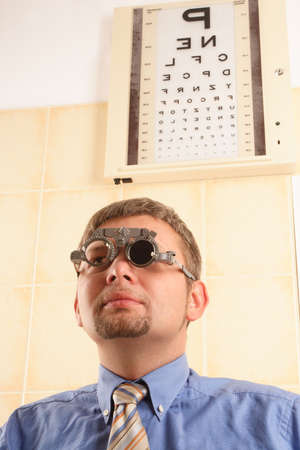 hyperopia: Male patient reading letters from the chart at the optician office