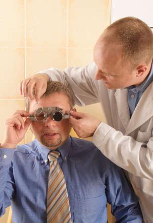 hyperopia: Ottico alla ricerca di una corretta occhiali per la sua paziente di sesso maschile  Archivio Fotografico