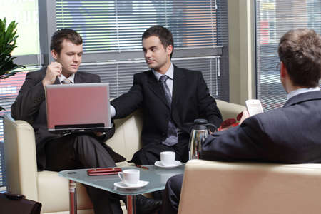 Three young business men sitting on leather sofa and working at laptop and palmtop in the office  photo