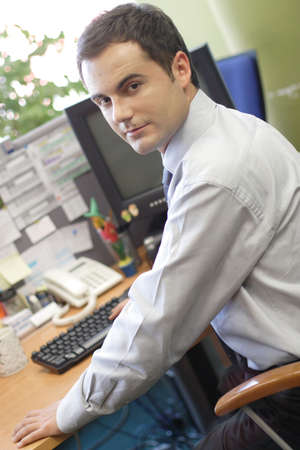 Young white man siiting at the desk and working on personal computer