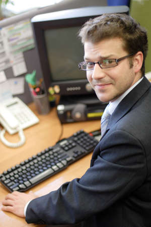 Young white man sitting at the desk and working on personal computer Stock Photo - 812884