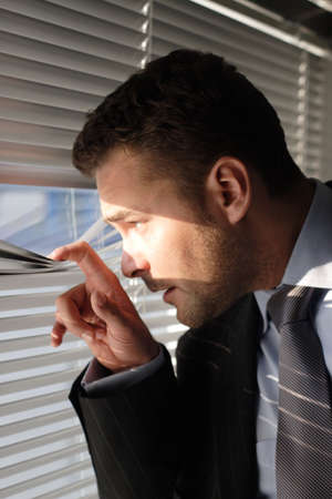 Handsome secret man looking through window blinds - left profile