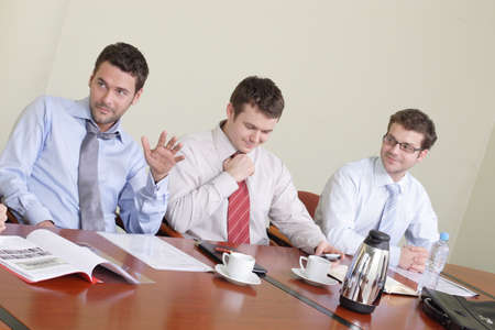 informal: Three businessmen sitting at a table conducting an informal conference. Stock Photo