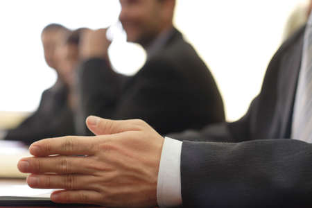 deliberation: Close-up of an arm in business attire, with businessmen in background  Stock Photo