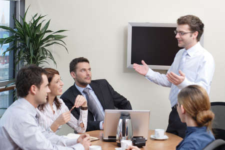 Business man making presentation on plasma screen to the group of people Stock Photo