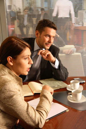 chief executive officers: Business man and woman sitting at the desk in the office and having meeting