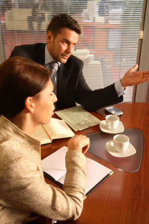 Business man and woman sitting at the desk in the office and having meeting,other woman in the background Stock Photo - 1186666