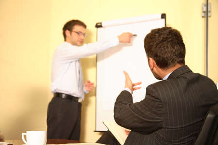 Presentation. one business man showing data on a chart to another. other one is speaking. Stock Photo - 1186668