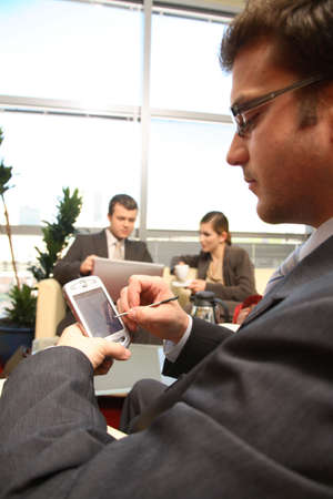 Three young business people working in the office. One solving problem, with palmtop in focuss photo