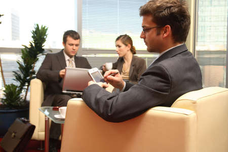 solving problem: Three young business people working in the office. One solving problem, with palmtop in focuss