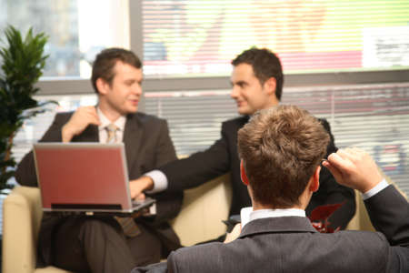 palmtop: Three young business men working in the office. One solving problem, with palmtop in focuss Stock Photo