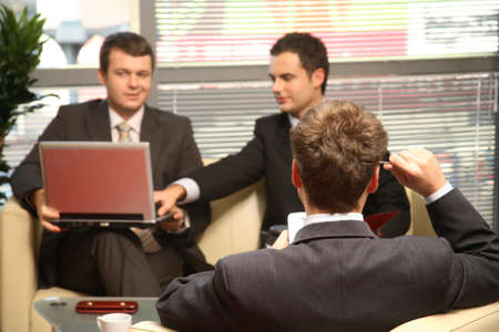 relations: Three young business men working in the office. One solving problem, with palmtop in focuss Stock Photo