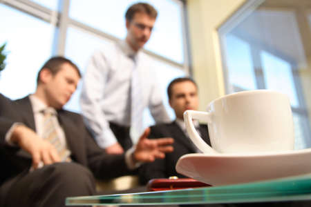 Three young business men meeting at the office. cup in focus.  photo