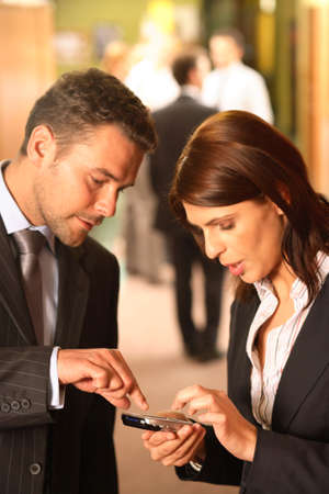 develope: Two business partners check their latest email messages on a PDA during a break from a business meeting.