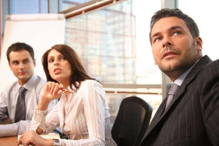 recolectar: Un grupo de hombres de negocios se re�nen en torno a una mesa de la sala de conferencias para un plan de trabajo para la discusi�n de un nuevo proyecto.  Foto de archivo