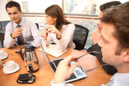 recolectar: Un grupo de cuatro personas del negocio recolecta alrededor de una tabla de la sala de conferencias para que una discusi�n de trabajo planee un nuevo proyecto.