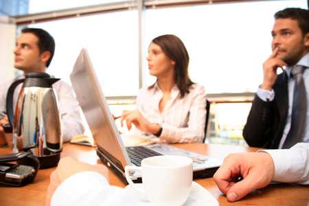 recolectar: Un grupo de gente del negocio recolecta alrededor de una tabla de la sala de conferencias para que una discusi�n de trabajo planee un nuevo proyecto. Foto de archivo