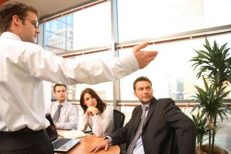 recolectar: Un grupo de cuatro hombres de negocios se re�nen en torno a una mesa de la sala de conferencias para un plan de trabajo para la discusi�n de un nuevo proyecto.  Foto de archivo
