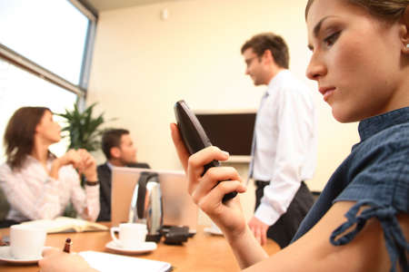 A group of executives discuss a project in an office meeting while one sits apart and stares at his mobile phone. Stock Photo - 1405574
