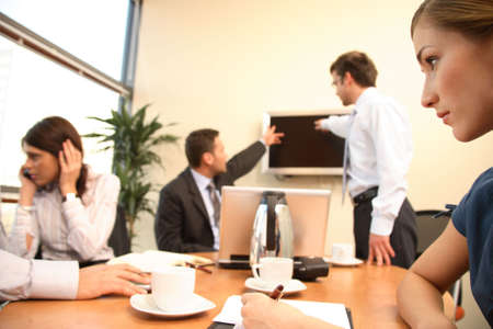 jornada de trabajo: grupo de cuatro hombres de negocios en el trabajo. una mujer est� llamando a un tel�fono, otra es hacer notas, dos hombres hablando de datos en pantalla de televisi�n.  Foto de archivo