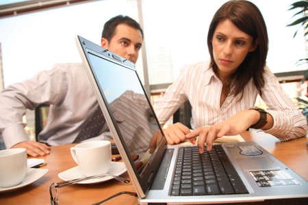 Professionals working with laptop in sunny office