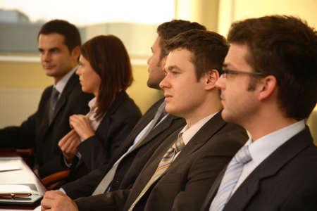 reunion de trabajo: Cinco personas de negocios de traje sentado en una mesa de conferencias, participando en una reuni�n y  o presentaci�n.
