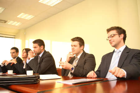 deliberation: Five business persons in suits sitting at a conference table, taking part in a meeting andor presentation.  Stock Photo