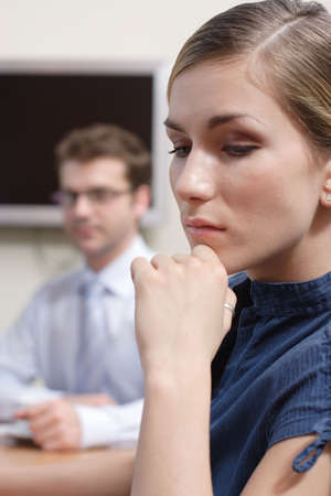 man looking at young sad woman in an office Stock Photo