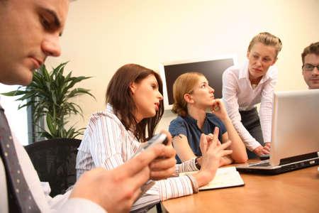 discutere: Un gruppo dei quadri discute un progetto in una riunione dellufficio mentre una si siede a parte e stares al suo telefono mobile.