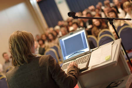 conventions:   Business woman at podium with laptop computer lecturing audience in auditorium