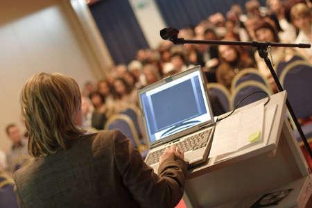 auditorium:   Business woman at podium with laptop computer lecturing audience in auditorium