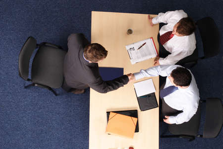 Three men having a business meeting.handshake .Aerial shot taken from directly above the table. photo